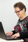 Donna anziana che lavora al computer portatile Immagine Stock