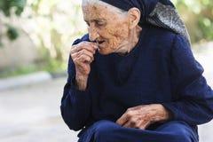 Donna anziana che mangia ciliegia Fotografie Stock Libere da Diritti