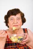 Donna anziana che mangia insalata Immagine Stock