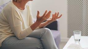 Donna anziana che parla e che gesturing durante la sessione di terapia con lo psicologo stock footage