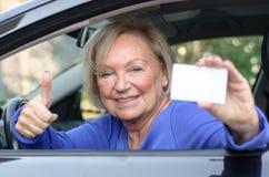 Donna anziana che pende da un'automobile che mostra la sua autorizzazione Fotografia Stock