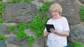 Donna anziana che per mezzo del computer della compressa Parete d'annata della pietra selvaggia nei precedenti stock footage