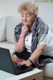 Donna anziana che per mezzo del computer portatile Fotografie Stock Libere da Diritti