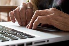 Donna anziana che per mezzo del computer portatile Immagine Stock