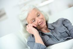 Donna anziana che per mezzo del telefono fotografie stock libere da diritti
