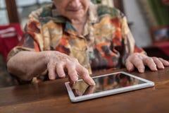 Donna anziana che per mezzo di una compressa Fotografia Stock Libera da Diritti