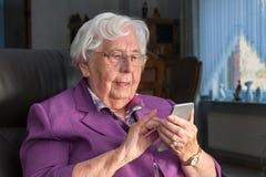 Donna anziana che per mezzo di uno smartphone fotografia stock