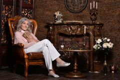 Donna anziana che posa nella sala Immagini Stock