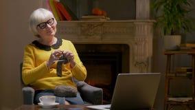 Donna anziana che riposa nel salone accogliente dell'appartamento stock footage
