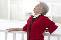 Donna anziana che ritiene indisposta con dolore alla schiena fotografie stock