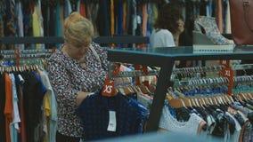 Donna anziana che sceglie i nuovi vestiti in deposito video d archivio