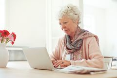 Donna anziana che scrive qualcosa a macchina Fotografia Stock Libera da Diritti