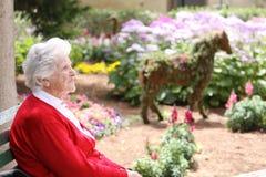 Donna anziana che si siede al sole Fotografia Stock Libera da Diritti