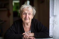 Donna anziana che si siede alla tavola nella stanza Fotografia Stock Libera da Diritti