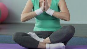 Donna anziana che si siede a gambe accavallate sulla stuoia di yoga, benessere del corpo, equilibrio interno archivi video