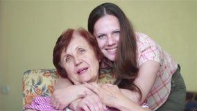 Donna anziana che si siede nella sedia che abbraccia la sua ragazza archivi video