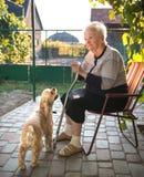 Donna anziana che si siede su una sedia con una canna Fotografia Stock