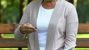 Donna anziana che si siede sul banco e sulla scatola d'apertura con il pendente, memorie felici calde archivi video