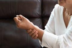 Donna anziana che soffre dal dolore della mano del polso, concetto di problema sanitario immagine stock libera da diritti