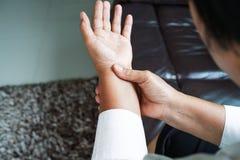 Donna anziana che soffre dal dolore della mano del polso, concetto di problema sanitario fotografie stock