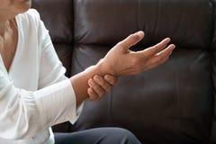 Donna anziana che soffre dal dolore della mano del polso, concetto di problema sanitario immagini stock