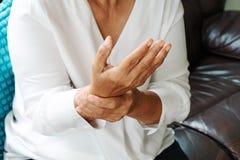 Donna anziana che soffre dal dolore della mano del polso, concetto di problema sanitario immagine stock