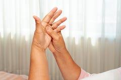 Donna anziana che soffre dal dolore della mano del polso, concetto di problema sanitario fotografia stock