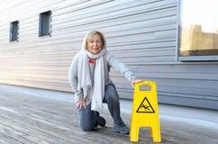 Donna anziana che striscia sulle sue ginocchia dopo avere slittato immagini stock