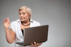 Donna anziana che tiene il computer portatile Fotografia Stock