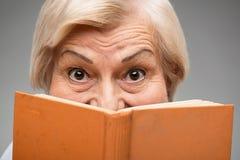 Donna anziana che tiene libro giallo Immagine Stock