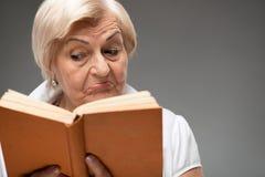 Donna anziana che tiene libro giallo Fotografia Stock