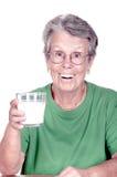 Donna anziana che tiene un bicchiere di latte fotografia stock