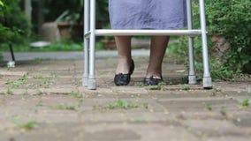 Donna anziana che usando un camminatore video d archivio