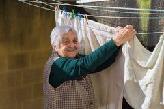 Donna anziana che va in giro il lavaggio sul terrazzo Immagini Stock