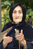 Donna anziana con i branelli che gesticulating Fotografie Stock