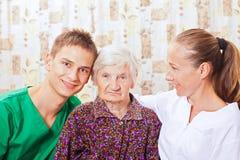 Donna anziana con i giovani medici Immagini Stock
