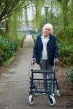 Donna anziana con il camminatore Immagini Stock