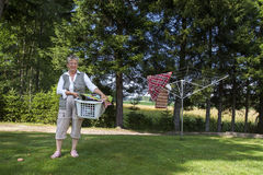 Donna anziana con il canestro di lavanderia Immagine Stock