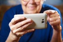 Donna anziana con il computer della compressa Immagine Stock