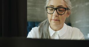 Donna anziana con il computer portatile video d archivio