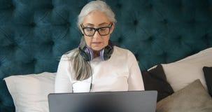 Donna anziana con il computer portatile in camera da letto stock footage