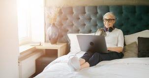 Donna anziana con il computer portatile in camera da letto archivi video