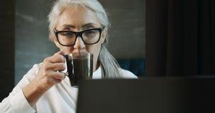 Donna anziana con il computer portatile ed il caffè archivi video