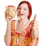 Donna con la tenuta del porcellino salvadanaio Fotografie Stock