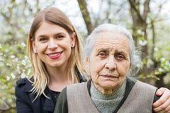 Donna anziana con il suo personale sanitario all'aperto immagini stock
