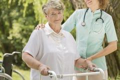 Donna anziana con l'infermiere che la aiuta fotografia stock