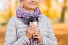 Donna anziana con la bevanda calda in chiavetta al parco di autunno fotografie stock
