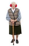 Donna anziana con la cuffia d'uso della canna di una pelliccia del faux Immagine Stock Libera da Diritti