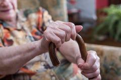 Donna anziana con le sue mani su una canna Fotografia Stock