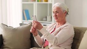 Donna anziana con lo smartphone che ha video chiacchierata video d archivio